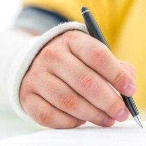 braccio ingessato con mano che firma un documento, penna